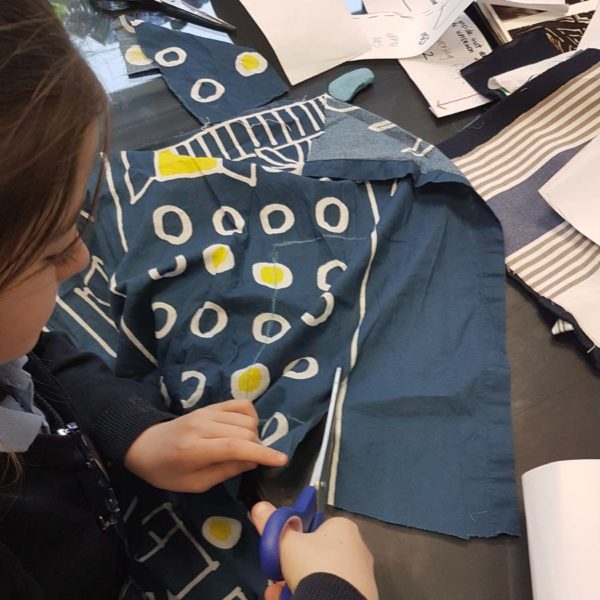cutting out fabric pieces in our machine sewing class